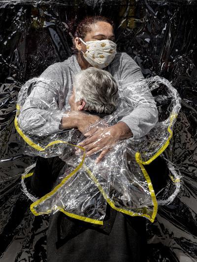 """Mads Nissen, """"Pierwszy uścisk""""– zdjęcie roku 2021 i najlepsze zdjęcie w kategorii """"News – zdjęcia pojedyncze"""". Duński fotograf uwiecznił pielęgniarkę Adrianę Silva da Costa Souzai 85-letnią Rosę Luzia Lunardi, dla której to była pierwsza możliwość przytulenia się do człowieka od pięciu miesięcy. Domy opieki w Brazylii zostały zamknięte dla osób z zewnątrz ze względu na pandemię, a personel dostał polecenie ograniczenia kontaktu fizycznego z podopiecznymi. Foliowa """"kurtyna do przytulania"""" umożliwiła przywrócenie tego kontaktu. Sao Paulo, 5 sierpnia 2020 r."""