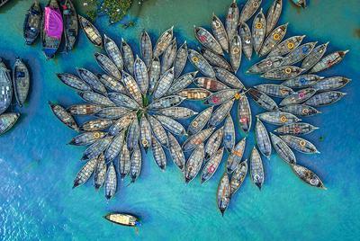 9 września 2021 r., Dhaka, Bangladesz. Widok z lotu ptaka na setki drewnianych łodzi w porcie rzeki Buriganga. Łodzie ozdobione kolorowymi wzorzystymi dywanikami codziennie dowożą do pracy miliony robotników mieszkających na obrzeżach miasta Dhaka.