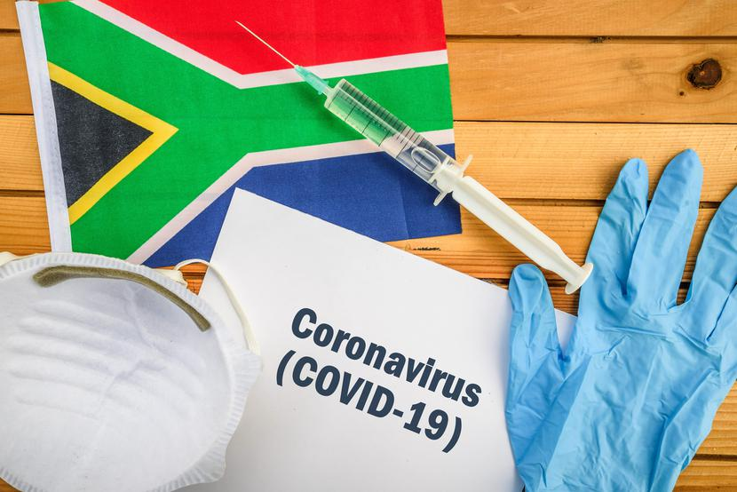 Flag of South Africa, vaccine, face mask for virus, glove and paper sheet with words Coronavirus COVID-19