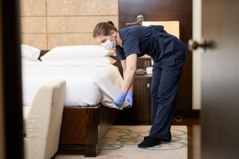 Opened door to hotel room with chambermaid in protective gloves making a bed in bedroom. Hotel service concept