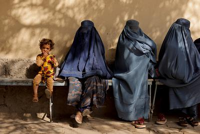 Kabul, Afganistan, 5 października 2021 r. Dziewczynka i kobiety w burkach siedzące przed szpitalem.