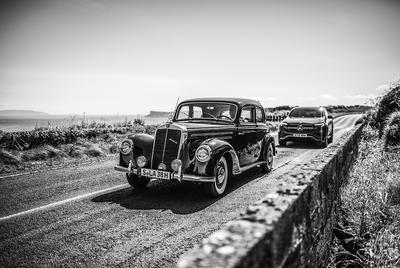 """Ein Oldtimer, der Mercedes-Benz W 187 aus dem Jahr 1951 faehrt entlang einer Kuestenstrasse bei Portrush, Nordirland, gefolgt von einem Mercedes-Benz EQC 400 4MATIC. 1951 fand """"The Open"""" das letzte mal in Portrush/ Nordirland statt. ;Stromverbrauch kombiniert: 20,8–19,7 kWh/100 km; CO₂-Emissionen kombiniert: 0 g/km*A Mercedes-Benz Classic car, the Mercedes-Benz W 187 from 1951 seen at a scenic road close to Portrush, followed by the Mercedes-Benz EQC 400 4MATIC. 1951 was the last time, that """"The Open"""" took place in Portrush/Northern Ireland.;Powerconsumption combined : 20,8–19,7 kWh/100 km; CO₂-Emissions combined: 0 g/km*"""