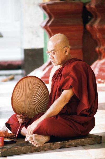 Mnich modlący się na terenie świątyni Szwedagon. Mnisi stanowią potężną siłę polityczną w Birmie. W roku 2007 wzniecili tzw. szafranową rewolucję. Powodem ich protestu były podwyżki cen paliwa, które pociągnęły drastyczny wzrost cen żywności. Apelowali także o podjęcie dialogu z opozycją