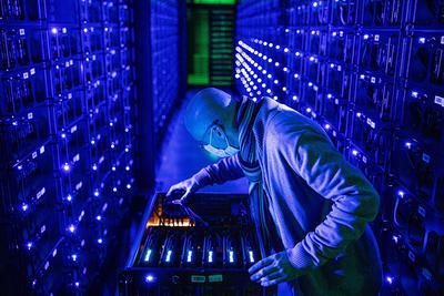 Pracownik w masce ochronnej przeprowadza inspekcję procesorów graficznych (GPU) firmy Sapphire Technology Ltd. na farmie kryptowalut Evobits w rumuńskim mieście Kluż-Napoka w środę 22 stycznia 2020 r. Druga najcenniejsza kryptowaluta na świecie, Ethereum, zyskała w tym roku 75 proc., wyprzedzając większego rywala Bitcoina.