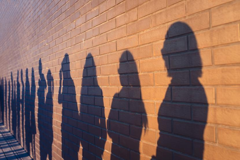 listopad 2020 People crowd shadows lined up against a red brick wall. They are in a queue for changes in life. Social distance, covid and immigration issue concept. Tłum bezrobocie bezrobotni cienie grupa ludzi covid-19 koronawirus